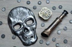En skallemaskering, kompasset och en monokel med leksaken piratkopierar mynt royaltyfri foto