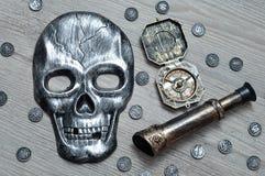En skallemaskering, kompasset och en monokel med leksaken piratkopierar mynt arkivbilder