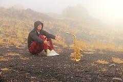 En skallig man spelar på en guld- alt- saxofon i naturen, mot royaltyfria foton