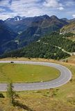 En skarp vänd på Grossglockner Alpenstrasse med Hohe Tauern i bakgrunden Royaltyfri Foto