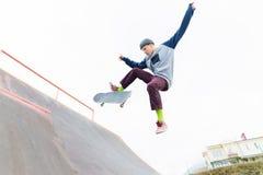 En skateboardertonåring i en hatt gör ett trick med ett hopp på rampen En skateboarder flyger i luften royaltyfria foton