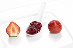 En sked av jordgubbedriftstopp och en jordgubbe på en platta Royaltyfri Foto