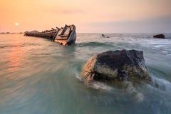 En skeppsbrott med vaggar stenen på stranden Arkivfoto