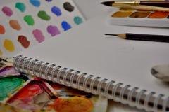 En sketchbook med paletten i olika färger och asken av vattenfärgmålarfärger med borstar och blyertspennan arkivbilder