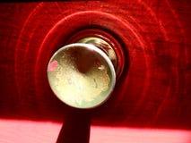 En skimrande röd dörr med en frasig guld- knopp royaltyfria foton