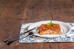 En skiva av lasagner på en wood tabell Royaltyfria Foton