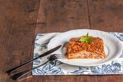 En skiva av lasagner på en wood tabell Arkivfoto