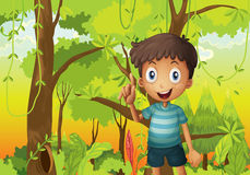 En skog med en ung pojke som bär en bandtshirt Arkivfoto