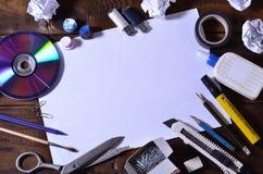En skola- eller kontorsstilleben med ett vitt tomt ark av papper och många kontorstillförsel Skolatillförselna ligger på ett brun royaltyfri foto