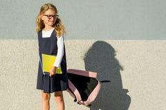 En skolflicka av grundskola för barn mellan 5 och 11 år med anteckningsböcker i hans hand Arkivfoto