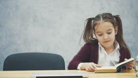 En skolflicka sitter p? tabellen Under denna tid väljer en bok eller en bärbar dator Lyckligt p? en gr? bakgrund ?ppnar lager videofilmer