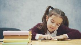 En skolflickaflicka sitter på en grå bakgrund Under denna tid läser skolpojken boken försiktigt flitig deltagare lager videofilmer