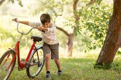 En skolpojke behas med en röd cykel i skogen eller garden arkivfoto