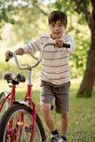 En skolpojke behas med en röd cykel i skogen eller garden arkivfoton