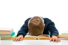 En skolpojke på en tabell på en tabell avverkar sovande, medan läsa, shoen Royaltyfri Foto