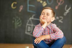 En skolpojke sitter på bakgrunden av en svart tavla som målas med chalks royaltyfria foton