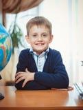 En skolpojke sitter på ett skrivbord arkivfoto
