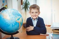 En skolpojke sitter på ett skrivbord fotografering för bildbyråer