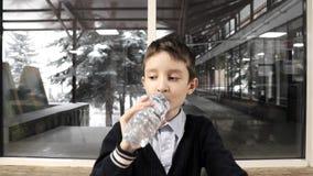 En skolpojke som sitter vid tabellen, tugga och dricksvattnet från den plast- flaskan arkivfilmer