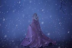 En skrämd flickablondin kör i en tjock dimma På älvan klär en lyxig rosa färg med ett långt drev och en regnrock där royaltyfri foto
