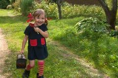 En skratta liten flicka som framlägger Pippi Longstocking, sitter på ett trädgårds- gräs och äter en klubba Royaltyfria Foton