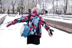 En skratta liten flicka som spelar med snö Arkivbild