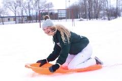 En skratta tonårs- flicka på en orange släde Fotografering för Bildbyråer