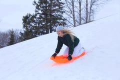 En skratta tonårs- flicka som glider ner en wintekulle Royaltyfri Foto