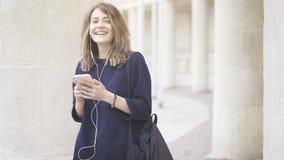 En skratta vit flicka för lycklig brunett lyssnar till musik utomhus Arkivbild