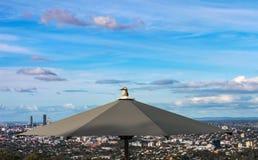 En skrattfågelfågel sätta sig överst av ett paraply på utkiken på Mt-sothönansom förbiser Brisbane i Queensland Australien arkivbild