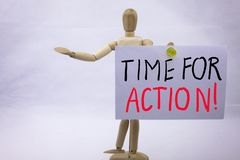 En skriftlig klibbig anmärkning för begreppsmässig gul inskrift för handhandstilöverskrift med ordet Tid för handling med svart f fotografering för bildbyråer