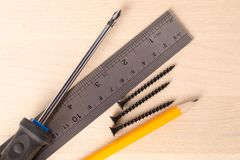 En skruvmejsel, en linjal, en blyertspenna och ligga för skruvar fotografering för bildbyråer