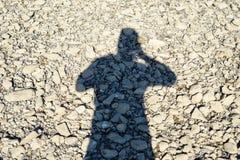 En skugga av en man på stenar som gör ett foto FlodRhen i Tyskland royaltyfri fotografi