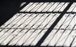 En skugga för staket för closeupavsnittmetall på trottoaren arkivbild