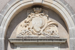 En skulpterad sköld och växtbevekelsegrunder dekorerar fasaden av en byggnad (Frankrike) arkivfoto
