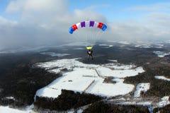 En skydiver lotsar en färg hoppa fallskärm i vinterhimlen royaltyfri fotografi