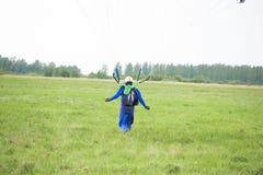 En skydiver som landas på ett fält Royaltyfri Fotografi