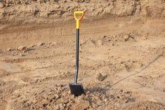En skyffel med det ljusa gula handtaget som klibbas till jordningen Malde arbeten, utgrävningar royaltyfri bild