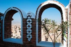 En skymt av dekorerade hus och slottar bak bågeväggen i den gamla staden av Sana'a, Yemen Arkivfoton