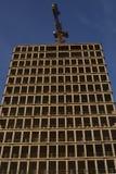 En skyskrapa som byggs med kranen royaltyfria foton
