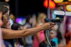 En skytte för ung kvinna med den halvautomatiska handeldvapnet för airsoft på en mässa arkivbilder