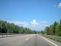 En slät plan huvudväg kör framåtriktat till och med skogen arkivfoton