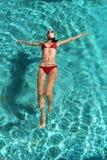 En slank sportig kvinna för härligt barn i en röd bikini kopplar av på azurvatten på en tropisk ö för dublin för bilstadsbegrepp  Royaltyfria Bilder