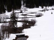 En slingrig flod i ett vitt vinterlandskap fotografering för bildbyråer