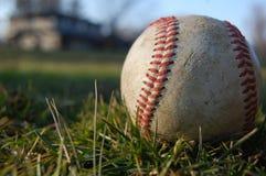 En sliten baseball i gräset Royaltyfria Foton