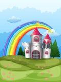 En slott på bergstoppet med en regnbåge Royaltyfri Fotografi