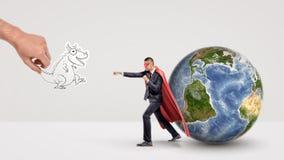 En småföretagare i superheroudde bredvid ett jordklot som var klart att slåss av en pappers- drake, rymde vid en jätte- hand Arkivbild