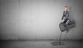 En småföretagare sitter på en svart trumma som läcker på olja som en häst Royaltyfria Foton