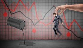En småföretagare som fångas av en jätte- manlig hand över en spillande olje- trumma och röda negativa ekonomiska grafer Arkivbild