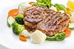 En smaklig mat. Grillade biffar och grönsaker.   Fotografering för Bildbyråer